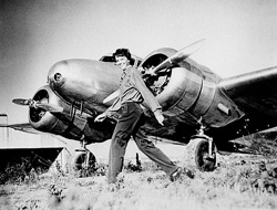 """Amelia Earhart strides confidently past her Electra """"Flying Laboratory,"""" supplied and equipped by Purdue University. Most of the interior was packed with extra fuel tanks rather than test tubes and dials, however."""