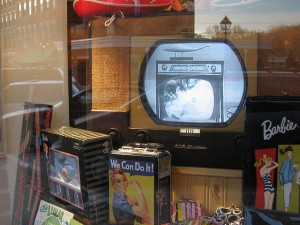 Here's a display of old-timey things, including an early television set.  Not so early, however, that it didn't have commercials.  This one, ironically, is advertising another vintage TV and console.  (Old Onliner, Flickr Creative Commons)