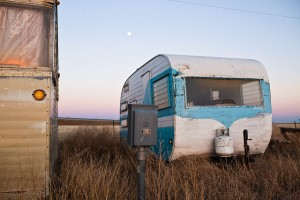 Things don't look so prosperous, in this row at least, at a trailer park on the edge of the prairie.  (Charles Henry, Flickr Creative Commons)