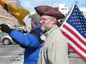 "The American Revolution gets its due at this rally in Anchorage, Alaska, with another flying of the ""Don't Tread on Me"" flag and the wearing of an early tri-corner hat.  (AP Photo)"