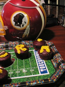 This Redskins helmet, with its Tuscan-red-colored warrior logo, is a centerpiece of this creative and tasty-looking display.  (littlerottenrobin, Flickr Creative Commons)