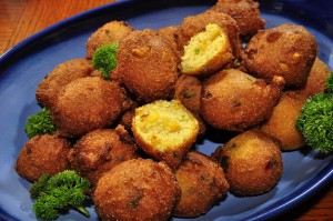 "A yummy plate of hushpuppies.  The term for these cornmeal treats is said to trace to a time when the family dog begged for something and was told, ""Hush, puppy!""  (jeffreyw, Flickr Creative Commons)"