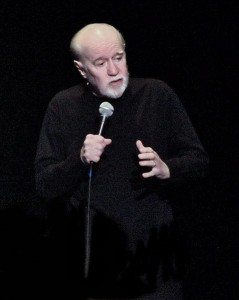 "Caustic comedians such as Lenny Bruce and George Carlin, shown here, popularized ""stand-up comedy"" in the 1970s.  Now there are comedy clubs worldwide.  (Wikipedia Commons)"