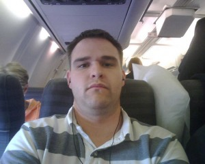This guy looks thrilled to have a middle seat.  (dipdewdog, Flickr Creative Commons)