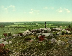 "An old photograph, colorized and made into a post card, of the view from Little Round Top onto another battle site called ""The Wheatfield.""  (Library of Congress)"