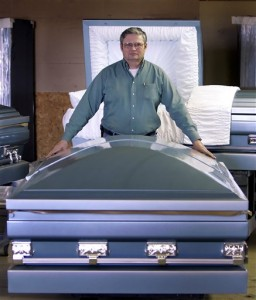 Keith Davis of the aptly named Goliath Casket Co. poses with one of its deluxe, extra-large models.  (AP Photo)