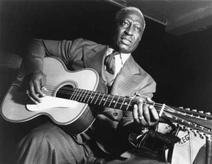 Lead Belly (his preferred spelling) was a 12-string guitar virtuoso as well as a powerful blues and folk singer.  (Wikipedia Commons)