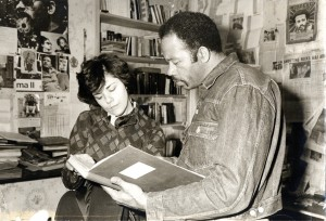Jane Friedman and Eldridge Cleaver look over something, perhaps a scrapbook, at his apartment in a working-class neighborhood of Paris. (courtesy, Jane Friedman)