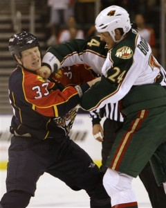 Wade Belak, left, absorbs a punch from Minnesota Wild enforcer Derek Boogaard, who, eerily, also died this summer.  Boogaard's death was ruled an accidental overdose of drugs and alcohol.  (AP Photo/Lynne Sladky)
