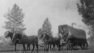 A family heads west in their Conestoga wagon that has all the conveniences!  Note the chimney.  (Library of Congress)