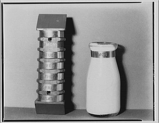 A returnable milk bottle circa 1920 with a stack of dayoftheweek bands