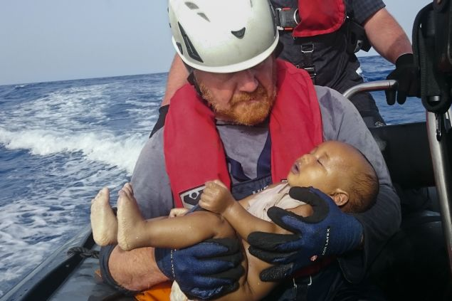 RECROP - In this Friday, May 27, 2016 photo, a Sea-Watch humanitarian organization crew member holds a drowned migrant baby, during a rescue operation off the coasts of Libya. Survivor accounts have pushed to more than 700 the number of migrants feared dead in Mediterranean Sea shipwrecks over three days in the past week, even as rescue ships saved thousands of others in daring operations. (Christian Buttner/EIKON NORD GMBH GERMANY via AP)