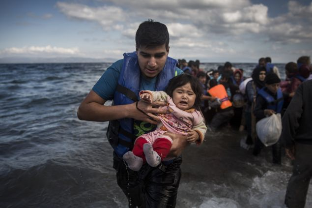 A man holding a baby disembarks from a dinghy after arriving from a Turkish coast to the northeastern Greek island of Lesbos, Sunday, Oct. 25, 2015. The International Office for Migration says Greece over the last week experienced the largest single weekly influx of migrants and refugees this year, at an average of some 9,600 per day. (AP Photo/Santi Palacios)