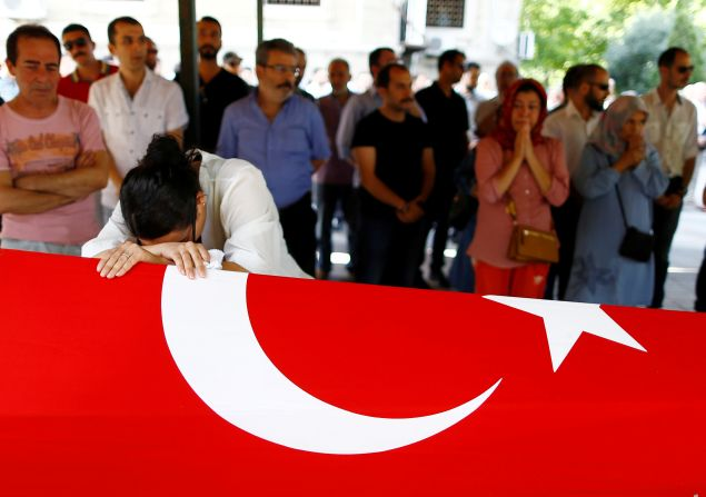A relative of Gulsen Bahadir, a victim of Tuesday's attack on Ataturk airport, mourns at her flag-draped coffin during her funeral ceremony in Istanbul, Turkey, June 29, 2016. REUTERS/Osman Orsal - RTX2IVPI