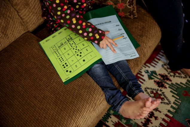 Five-year-old Syrian refugee Leen works on her homework at her new home in Sacramento, California, November 16, 2015. Leen and her family fled violence in Syria three and a half years ago and arrived in Sacramento in September after living in Jordan. Her face is excluded from the photo to protect his identity. To match Feature - FRANCE-SHOOTING/USA-MIGRANTS    REUTERS/Max Whittaker  - RTS7QW8