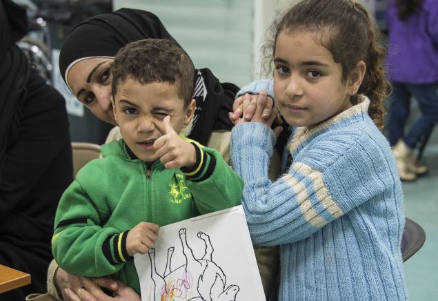 Two Syrian refugee children pose while their family undergoes medical screening before the beginning of an airlift to Canada, in Beirut, Lebanon December 9, 2015. The first plane load of Syrian refugees departed from Beirut on Thursday, aboard a military aircraft bound for Toronto. The Liberal government plans to resettle 10,000 refugees from Syria's four-year-old civil war by the end of the year and a further 15,000 by the end of February. Picture taken December 9, 2015.  REUTERS/Corporal Darcy Lefebvre/Canadian Forces Combat Camera/Handout via Reuters FOR EDITORIAL USE ONLY. NOT FOR SALE FOR MARKETING OR ADVERTISING CAMPAIGNS. THIS IMAGE HAS BEEN SUPPLIED BY A THIRD PARTY. IT IS DISTRIBUTED, EXACTLY AS RECEIVED BY REUTERS, AS A SERVICE TO CLIENTS - RTX1Y40I
