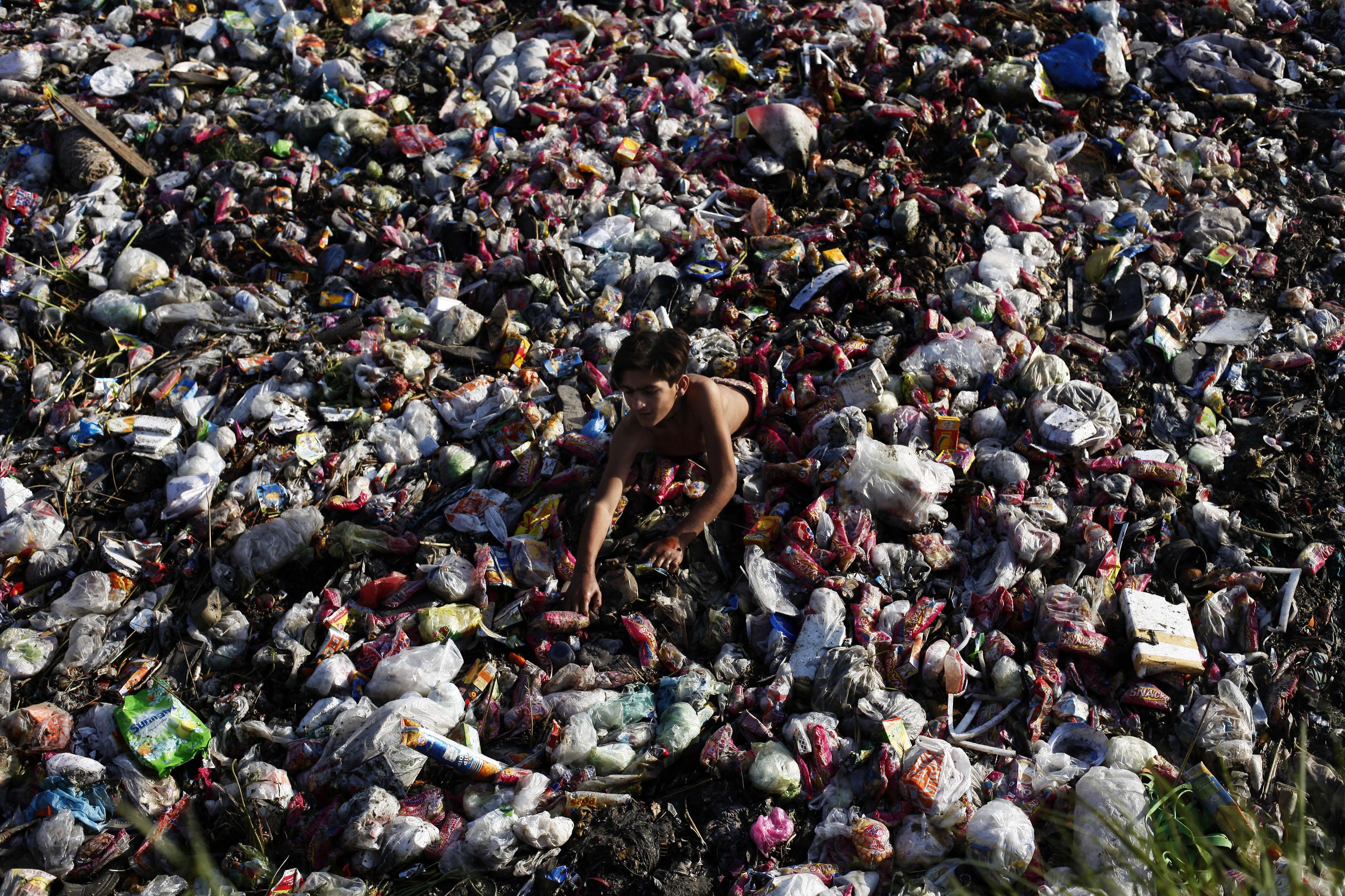 Lahor'da bir çocuk çöplerin arasından plastik atık topluyor