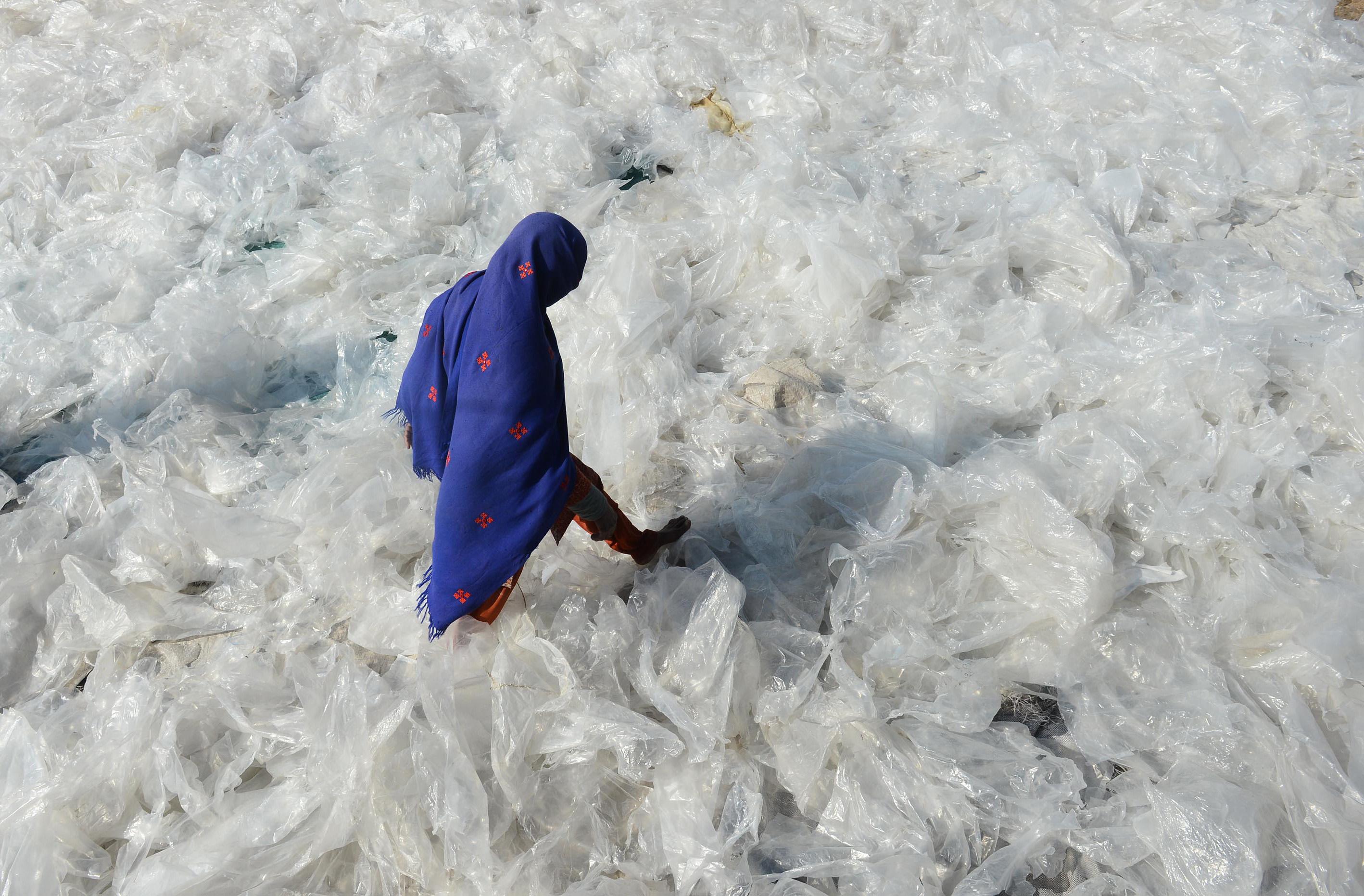 Pakistan'da bir kadın plastik torbaların üzerinde yürüyor