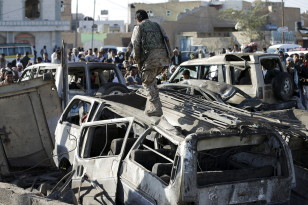 A Houthi fighter walks on a vehicle damaged by an air strike at a residential area near Yemen's Sanaa Airport March 26, 2015.