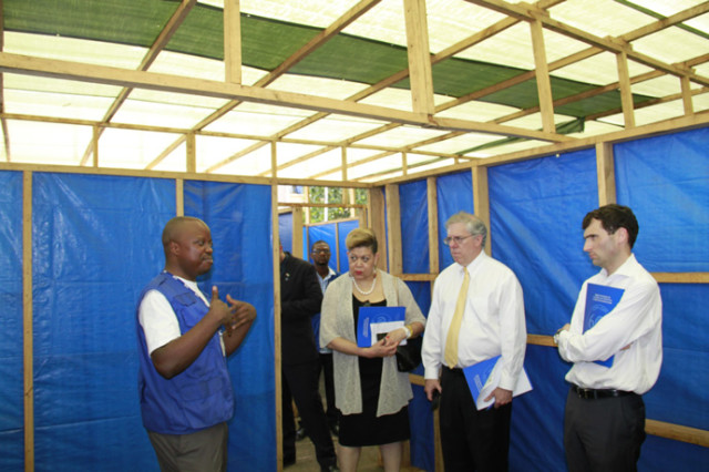Senior Ebola Coordinator Denise Rollins, Associate Administrator Eric Postel, and National Security Council Senior Advisor Chris Kirchhoff listen as a staff member from the International Organization for Migration provides a tour of a mock-Ebola treatment unit in Freetown, Sierra Leone. (courtesy of  Kate Alexander/ USAID)