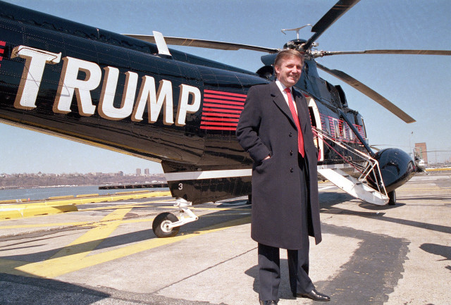 Real estate magnate Donald Trump poses in front of one of three Sikorsky helicopters at Port Authority in New York on March 22, 1988.  (AP)