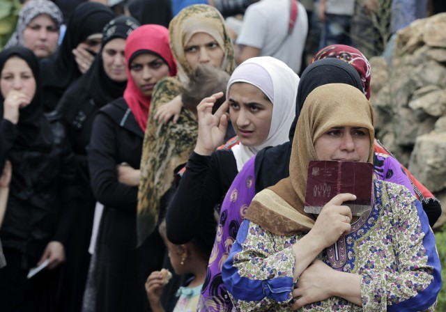 Syrian women wait in line to receive aid from an Islamic relief agency at a refugee camp in the town of Ketermaya in Lebanon on Sept. 7, 2015. (Reuters)