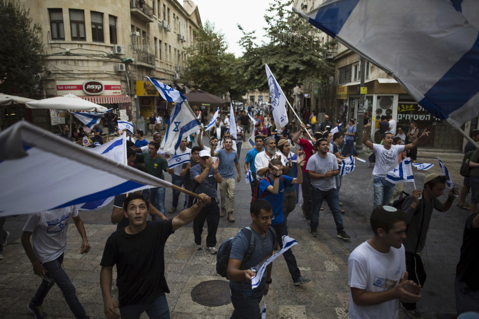 People sing and dance with Israeli national flags at a pedestrian street in downtown Jerusalem