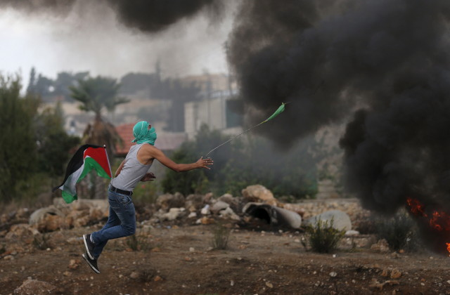 A Palestinian protester uses a sling to hurl stones towards Israeli troops during clashes near the Jewish settlement of Bet El, near the West Bank city of Ramallah on Oct. 18, 2015. (Reuters)