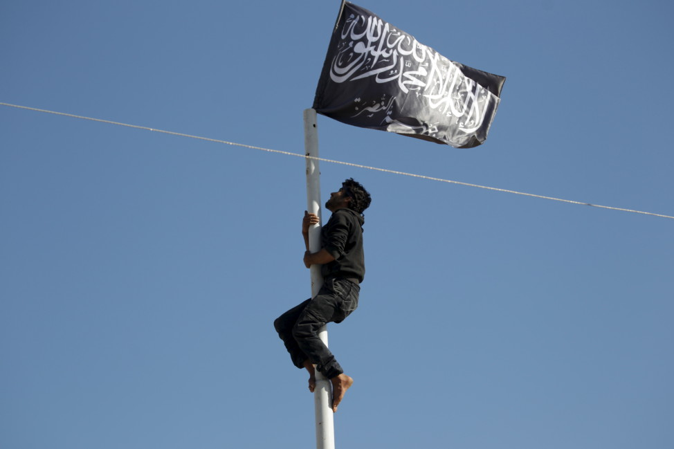 A member of al-Qaida's Nusra Front climbs a pole where the group's flag was raised in Ariha city after a coalition of insurgent groups seized the area in Syria's Idlib province on May 29, 2015. (Reuters)