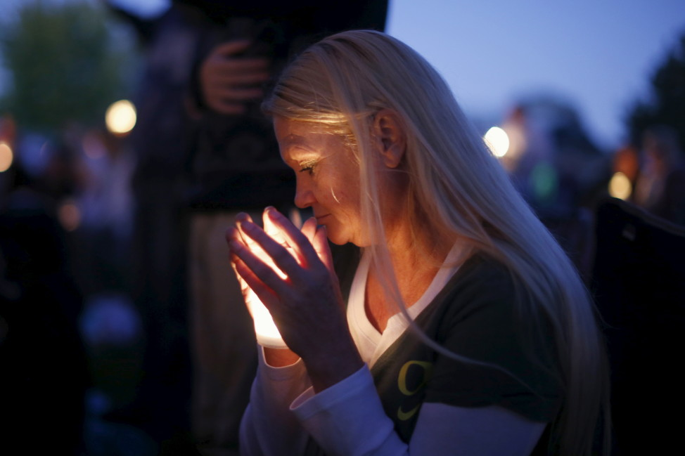 A woman takes part in a candlelight vigil for victims of the Umpqua Community College shooting, in Winston, Oregon on Oct. 3, 2015. (Reuters)