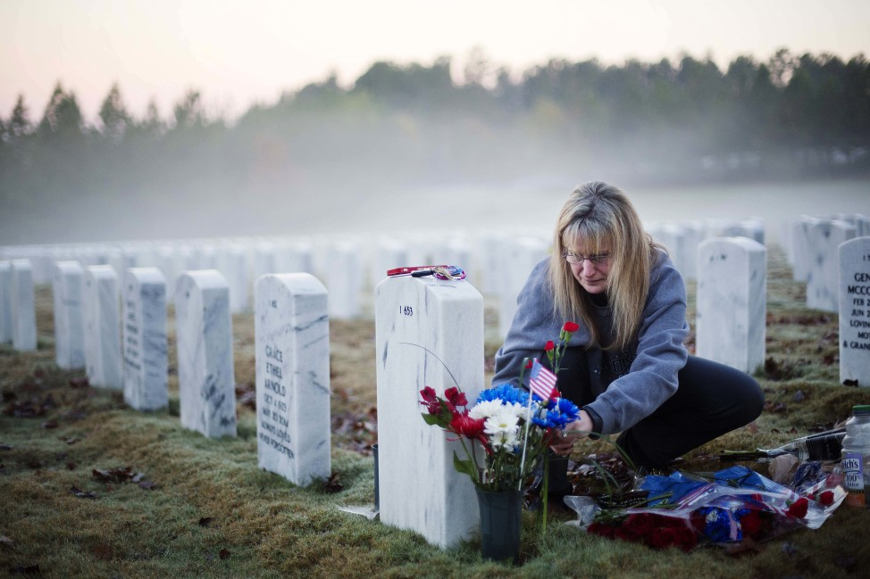 Jiffy Helton Sarver, of Monroe, Ga., places flowers at the grave of her son, 1st Lt. Joseph Helton, Jr., who was killed while serving in Iraq in 2009, at Georgia National Cemetery on Veterans Day, Nov. 11, 2015. (AP)