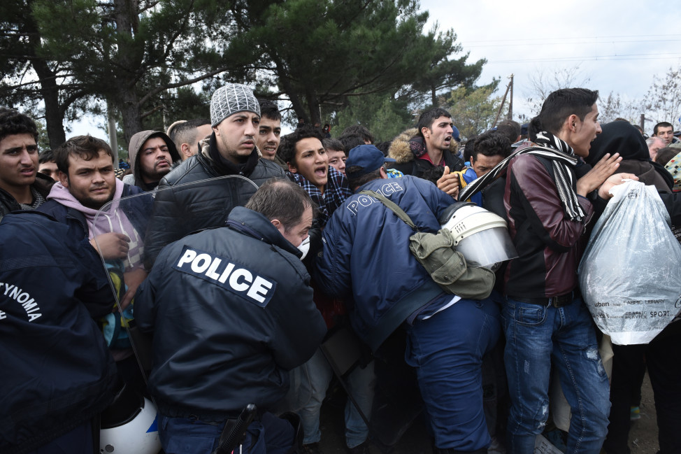 Refugees scuffle with the Greek police in their effort to reach the borderline with Macedonia, near the Greek village of Idomeni on Nov. 22, 2015. (Reuters)