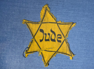 The Yellow Star badge of Heinz-Joachim Aris (Dresden 1941) reading 'Jew' is displayed  in a showcase in the new special exhibition 'Shoes of the Dead - Dresden and the Shoah' at the Military History Museum in Dresden, Germany on Jan. 22, 2014. (Reuters)