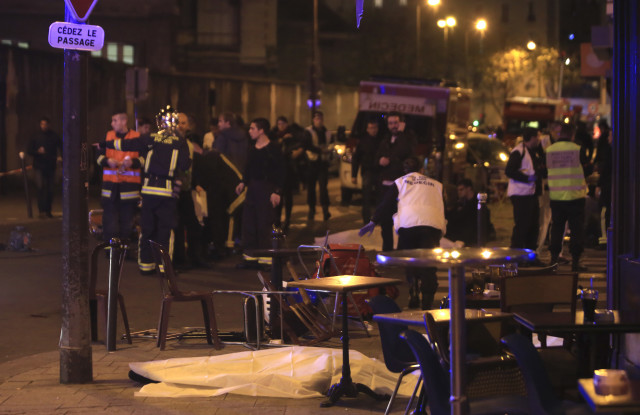 Rescue workers and medics work by victims in a Paris restaurant, Friday, Nov. 13, 2015. (AFP)