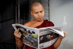 A Buddhist monk reads a newspaper on a street in Yangon on Nov, 9, 2015. (Reuters)
