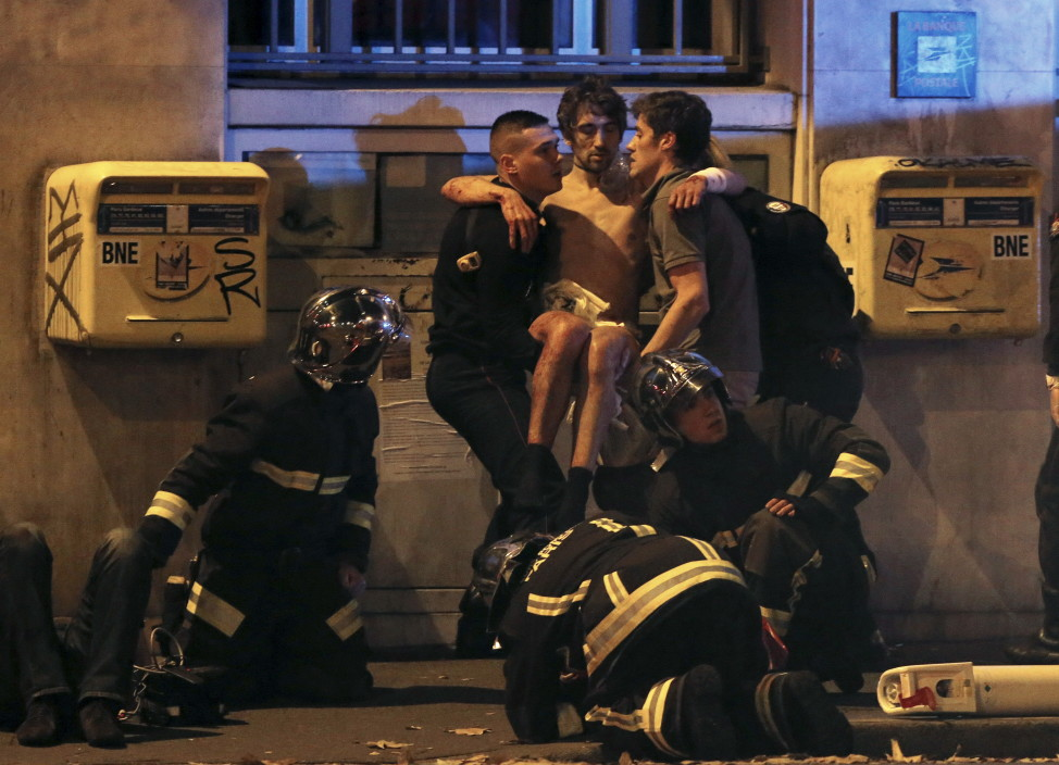French fire brigade members aid an injured person near the Bataclan concert hall after the fatal shootings in Paris on Nov. 13, 2015. (AP)