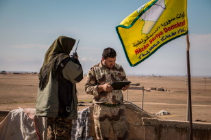 Rebel fighters form the Democratic Forces of Syria use a walkie talkie and a tablet near the al-Hawl region, where fighting between them and Islamic State fighters are taking place in southeastern city of Hasaka, Syria on Nov.10, 2015. (Reuters)