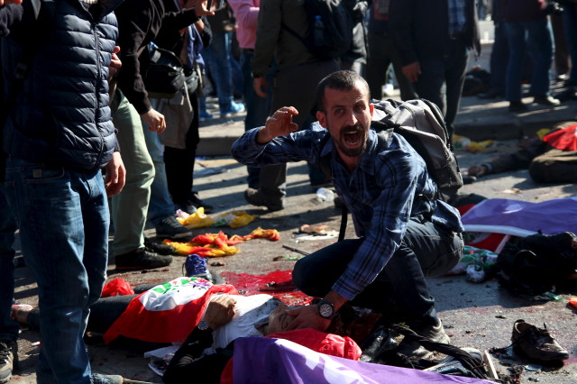 A man asks for help for an injured woman following deadly explosions during a peace march in Ankara, Turkey, Oct. 10, 2015.