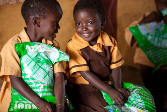 Students in Ghana hold insecticide-treated mosquito nets. (photo courtesy of PMI)