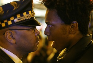 "Lamon Reccord, right, stares and yells at a Chicago police officer ""Shoot me 16 times"" as he and others march through Chicago on Nov. 25, 2015. (AP)"