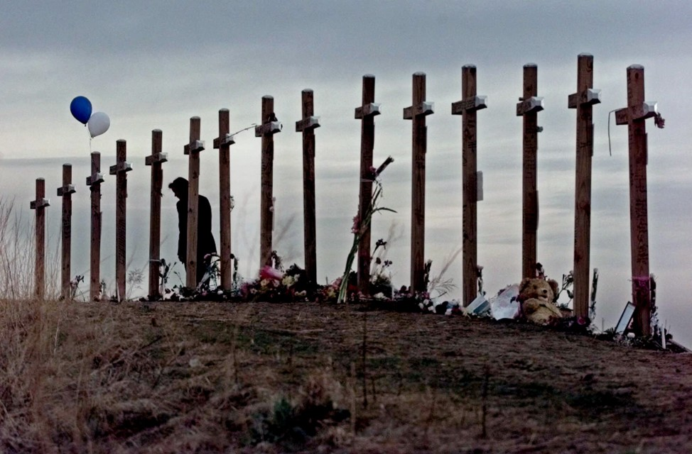 This April 28, 1999 file photo shows a woman standing among 15 crosses posted on a hill above Columbine High School in Littleton, Colo., in remembrance of the 15 people who died during a school shooting on April 20, 1999.  (AP)