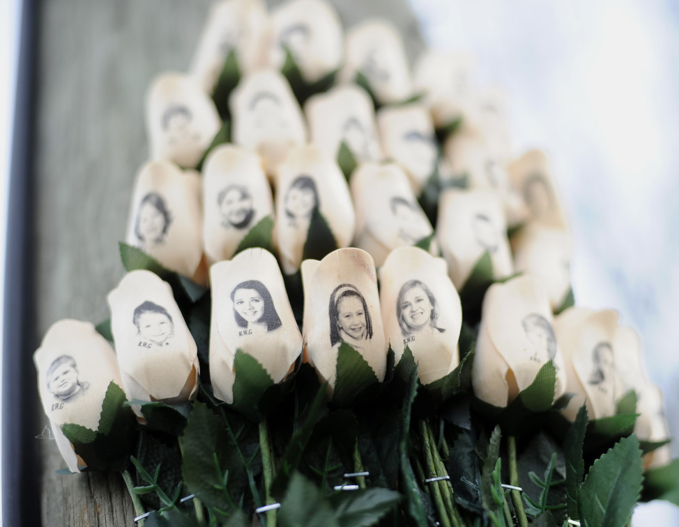 In this Jan. 14, 2013 file photo, white roses bearing the faces of victims of the Sandy Hook Elementary School shooting are displayed on a telephone pole near the school in Newtown, Conn. (AP)