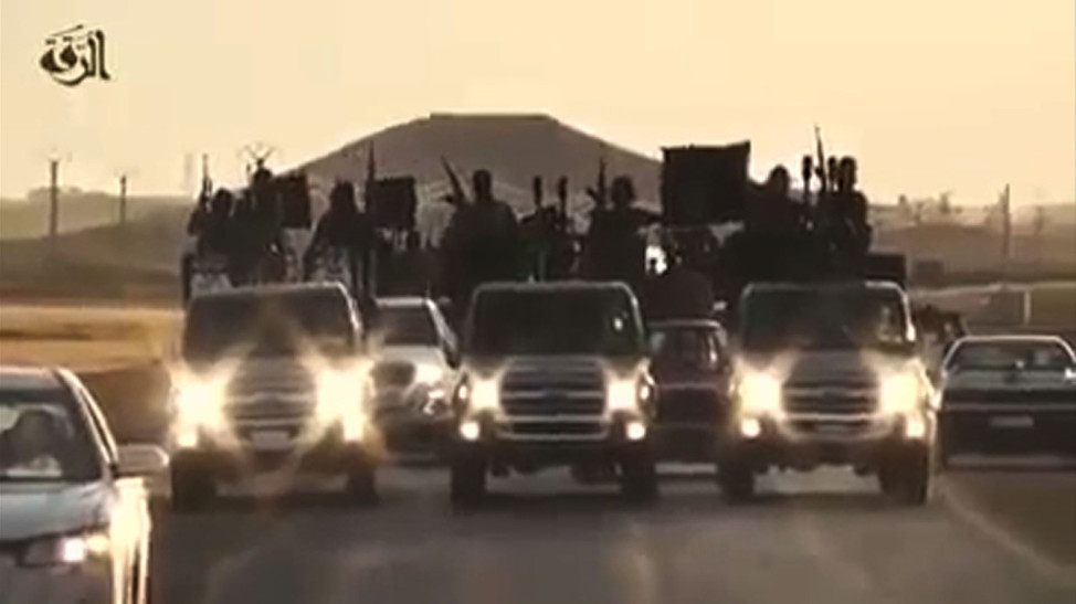 An image grab taken from a video released by Islamic State group's official Al-Raqqa site via YouTube on September 23, 2014, allegedly shows Islamic State (IS) group recruits riding in armed trucks in an unknown location.