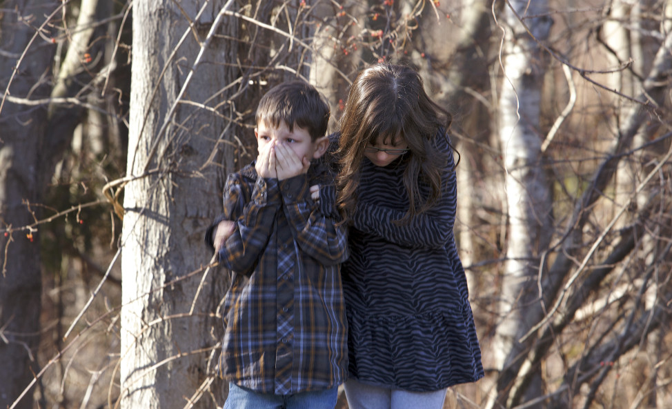 First-grader Henry Terifay and his sister, fourth-grader Kelly Terifay, wait outside Sandy Hook Elementary School after a shooting in Newtown, Connecticut, December 14, 2012. A shooter opened fire at the elementary school. REUTERS/