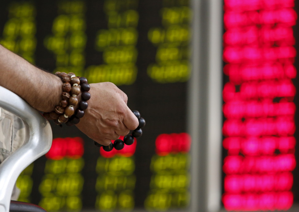 An investor holds onto prayer beads as he watches a board showing stock prices at a brokerage office in Beijing, China, July 6, 2015. (Reuters)