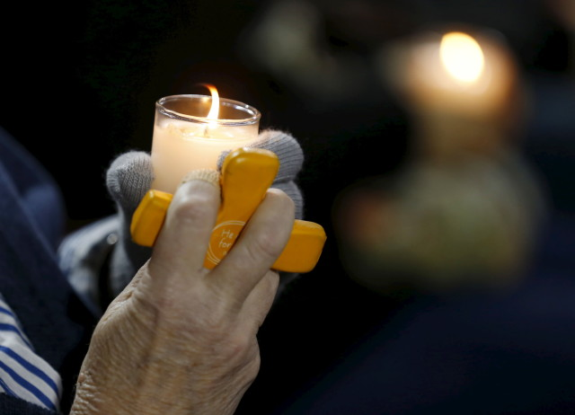 An attendee reflects on the tragedy of Wednesday's shooting attack, during a candlelight vigil in San Bernardino, California, December 3, 2015. REUTERS