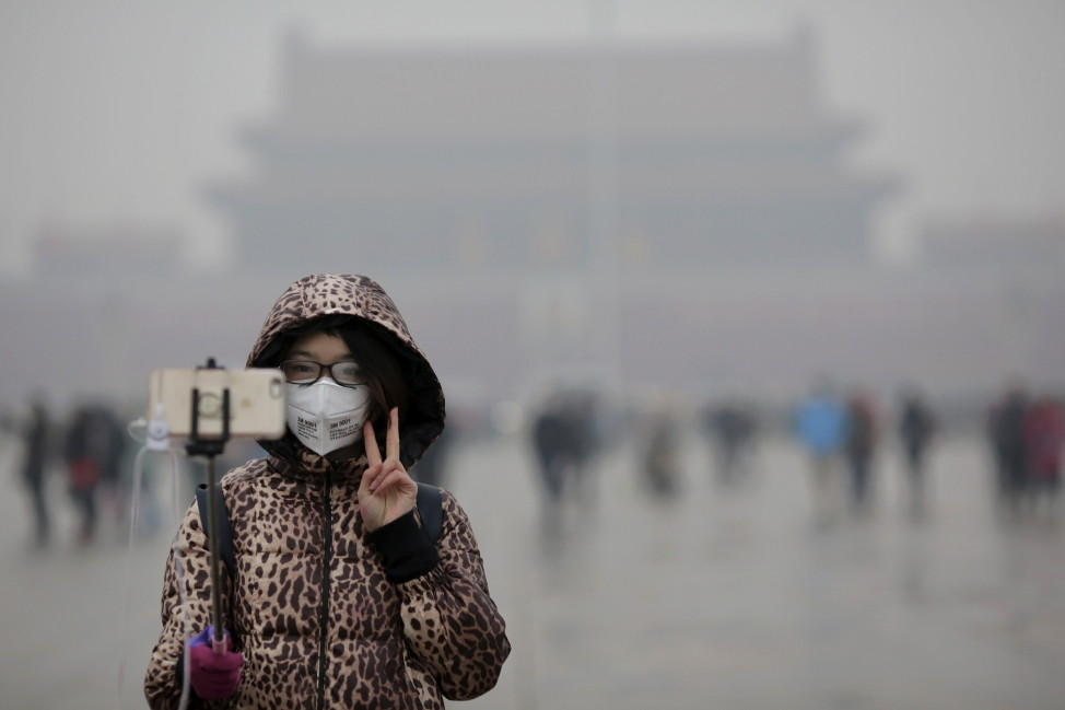 "A woman wearing a protective mask has her picture taken just after a flag-raising ceremony amid heavy smog at the Tiananmen Square, after the city issued its first ever ""red alert"" for air pollution, in Beijing December 9, 2015."
