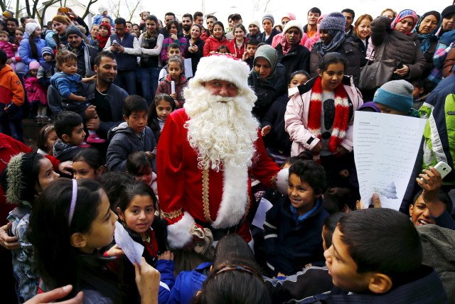 "Migrant children surround a volunteer dressed as Father Christmas during a Christmas gathering organized by local relief organization ""Die Johanniter"" at the refugee camp in Hanau, Germany, December 24, 2015. (REUTERS)"