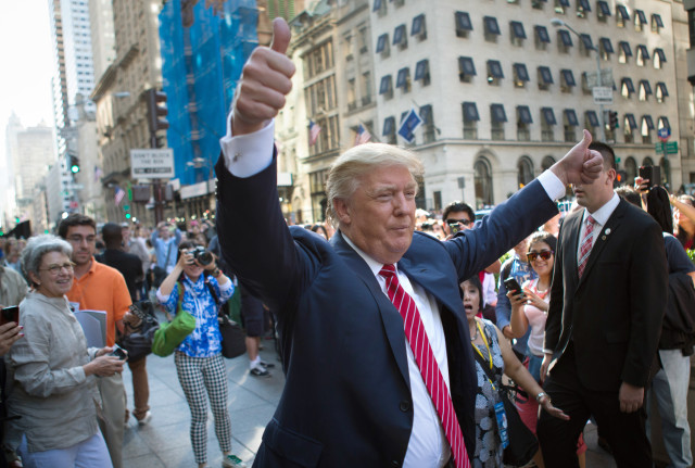 Republican presidential candidate Donald Trump waves to the crowd gathered in front of Trump Tower ahead of the arrival of the pope's motorcade for an appearance in New York's Central Park. September 24, 2015 (AP)