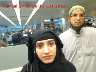 Tashfeen Malik, (L), and Syed Farook are pictured passing through Chicago's O'Hare International Airport in this July 27, 2014 handout photo obtained by Reuters.